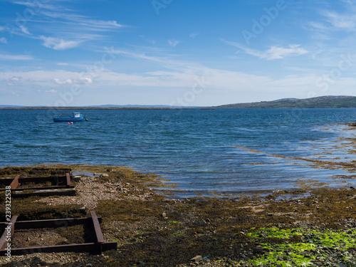 Fotografiet pier on the irish sea with fishing boat