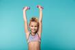 Leinwandbild Motiv Smiling little sports girl doing exercises with dumbbells