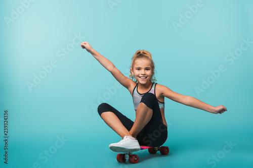 Fotobehang School de yoga Smiling little sports girl playing with a skateboard