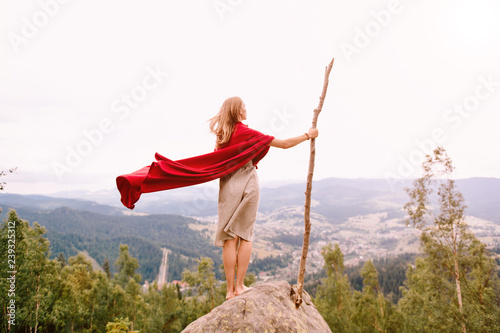 Papiers peints Blanc Unknown female in dress and red cape standing on stone at top of mountaing. Barefoot blonde woman with big wooden stick enjoying landscape from point of view. Girl in red cloak outdoor portrait.