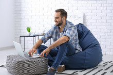 Young Man With Laptop Sitting On Beanbag Chair At Home