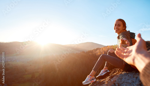 Keuken foto achterwand Ontspanning smiling woman hiker sits on edge of cliff against background of sunrise