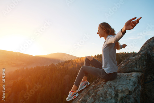 young woman sits on edge of cliff against background of sunrise