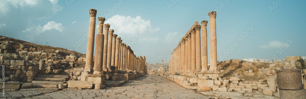 Fototapeta A view looking down the Cardo showing stone carved columns and paved street at the ancient city of Jarash or Gerasa, Jerash in Jordan. ancient Roman sights. Panorama.