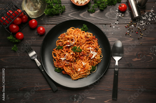Plate with delicious pasta bolognese on dark wooden table Wallpaper Mural