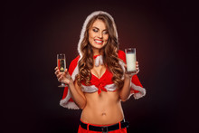 Christmas And New Year. Woman In Santa Costume With Hood Standing Isolated On Black With Glass Of Champagne Looking At Milk Playful