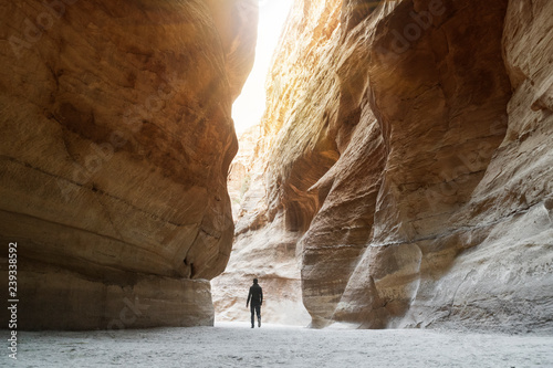 Fototapeta Tourist in narrow passage of rocks of Petra canyon in Jordan