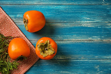 Tasty Ripe Persimmons On Color Wooden Table