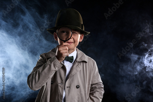 Fotografía Cute little detective with magnifying glass in smoke on dark background