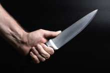 A Big Shiny Knife In Hand On A Black Background
