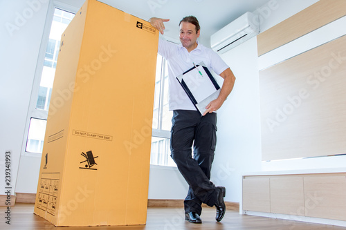 Obraz A man shows a large package in an empty room. The postman delivers the parcel to the new apartment. - fototapety do salonu