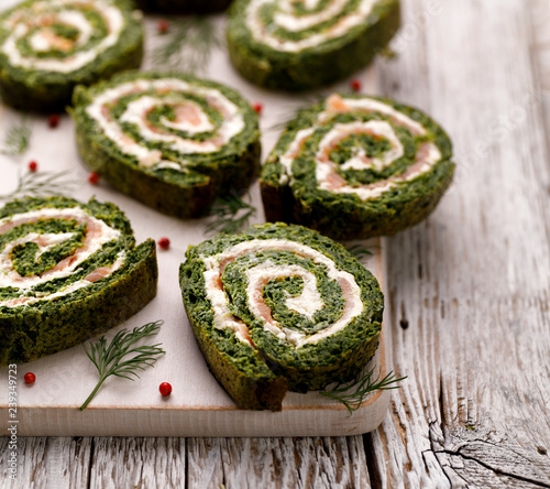 Fototapeta Spinach roulade stuffed with cream cheese and smoked salmon sliced on a white board