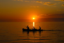 People Rowing Home At Sunset A...