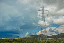 High Voltage Tower And Wires Above Tropic Forest In Highland Nature Landscape In Mediterranean District Of Earth Before Storm