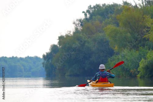 Fotografie, Obraz  Rear view of kayaker man paddle yellow kayak on Danube river