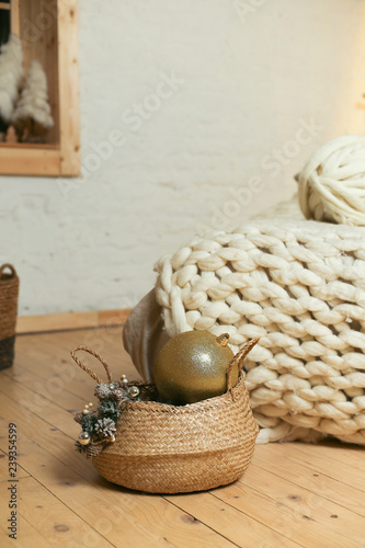 wicker basket with Christmas decoration near knitted white ...