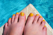 Pair Of Bare Feet With Yellow Nail Polish And A Toe Crystal At The Beach