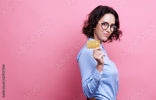 Valokuvatapetti portrait of smiling woman holding credit card in hand and looking to camera isol