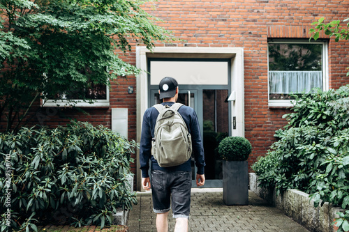 Foto  A tourist goes to the guesthouse or hostel in order to stay in a room that he booked or a student with a backpack returns home after his studies at the institute or on vacation
