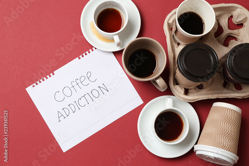 Fotografie, Obraz  Almost empty cups of coffee and paper sheet with text COFFEE ADDICTION on color