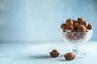 Leinwanddruck Bild - Glass bowl with sweet truffles on light background