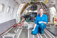 Woman Kneeling Inside Airplane