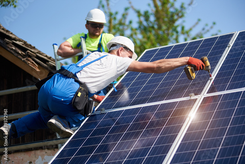 Fotografie, Tablou  Two workers technicians connecting heavy solar photo voltaic panels to high steel platform