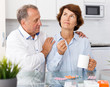 Mature family couple sitting at kitchen table and taking medicine indoors