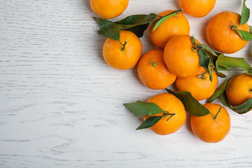 Fresh ripe tangerines and space for text on wooden background, top view