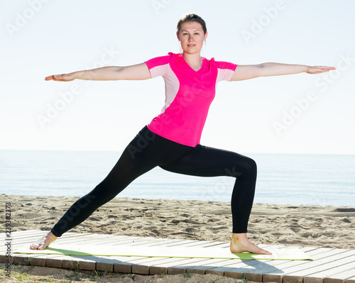 Woman exercising yoga poses on beach