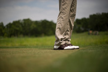 Man Wearing Golf Shoes On A Golfing Green.
