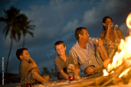 Portrait of a young boy sitting with his parents and younger brother on a beach next to a fire.