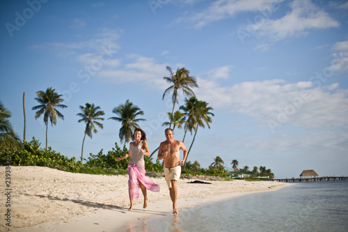 Mid-adult couple running along the beach.