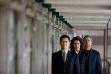 Mid-adult Business Woman Standing With Two Colleagues In A Derelict Prison.