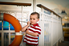 Young Boy Standing On The Deck Of A Boat.