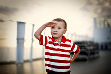 Young Boy Saluting While Stand...