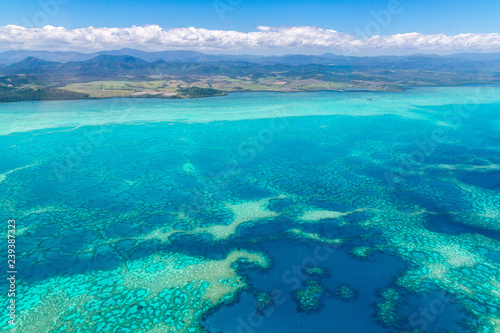 Leinwand Poster Aerial view of idyllic azure turquoise blue lagoon of West Coast barrier reef, with mountains far in the background, Coral sea, New Caledonia island, Melanesia, South Pacific Ocean