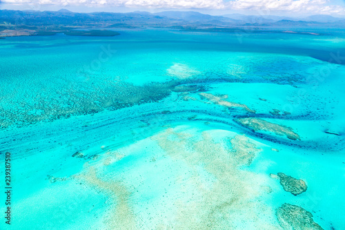 Photo  Aerial view of idyllic azure turquoise blue lagoon of West Coast barrier reef, with mountains far in the background, Coral sea, New Caledonia island, Melanesia, South Pacific Ocean