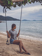 Young female with braided hair sitting on a beach swing in Thailand.