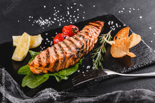 Grilled salmon fillet garnished with spinach, lemon, herbs on plate over wooden background Wallpaper Mural