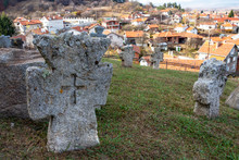 Close Picture Of Ancient Stone Crosses At The Churchyard Of St. Petka Eastern Orthodox Church In Tsari Mali Grad Fortress, The Village Of Belchin, Bulgaria In The Background