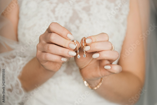 Cuadros en Lienzo Women's wedding jewelry (earrings) in the hands of the bride, selective focus