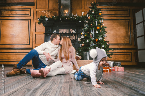 Fototapeten Tanzschule family holiday New Year and Christmas. Young caucasian family mom dad son 1 year sit wooden floor near fireplace christmas tree on Christmas evening. Baby learning walk creeps background parents