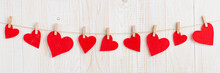 Red Hearts On A Rope With Clothespins, On A White Wooden Background. Place For Text, Copy Space.