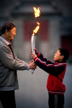 Mature Adult Man Holding A Lit Torch With His Grandson.
