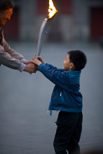 Young Boy Carrying An Olympic Torch In A Park.