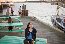 Thoughtful Woman Sitting On Picnic Table At Harbor During Sunset