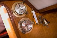 Barometer With A Bell And A Clock And Temperature Gauge On A Boat.
