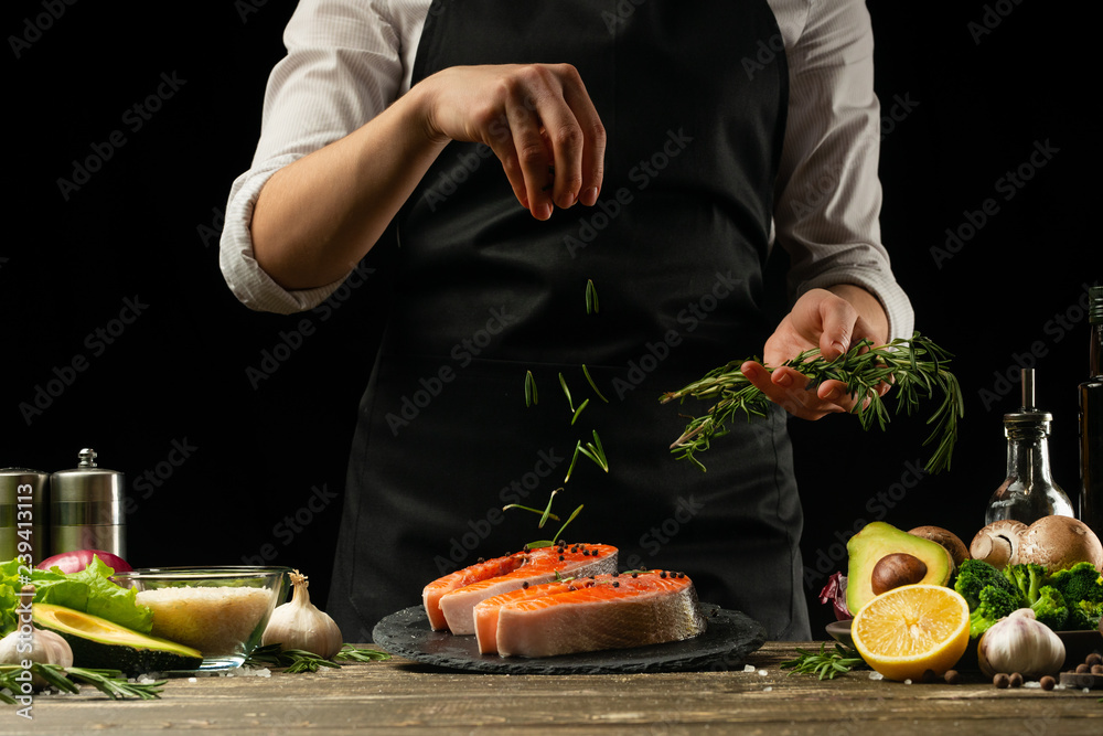 Fototapety, obrazy: The chef prepares fresh salmon fish, freshly salted trout, sprinkled with rosemary leaves with ingredients. Salmon steak, restaurants, hotel business, menu and recipe book