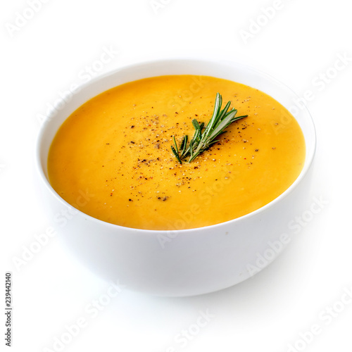 Bowl of pumpkin and carrot cream soup isolated on white background